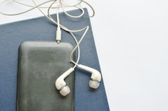 Book and earphones connect in smartphone on white background Stock Images