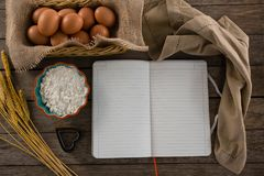 Book, eggs, flour, cookie cutter and cloth kept on a table Stock Photography