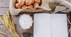 Book, eggs, flour, cookie cutter and wheat stem kept on a table 4k