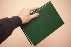 Book with empty dark green cover in male hand Stock Images