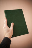 Book with empty dark green cover in male hand Royalty Free Stock Photo