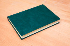 Book with empty dark green cover on wooden table Stock Photos