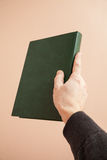 Book with empty dark green leather cover in hand Royalty Free Stock Photos
