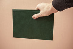 Book with empty green leather cover in hand Stock Photo