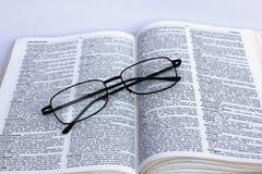 Book and eyeglass Stock Images