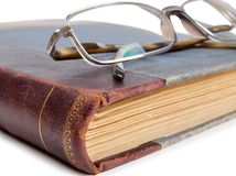 Book and eyeglasses Stock Photos