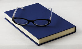 Book and eyeglasses Stock Images