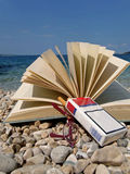 Book, eyeglasses, cigarette on beach Royalty Free Stock Photos