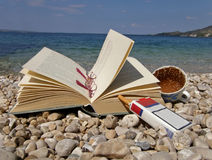 Book, eyeglasses, coffee, cigarette. Holiday - book, eyeglasses, cup of coffee, cigarette on stone-pebbles beach at Adriatic sea - Croatia - Dalmatia. Horizontal Stock Photography