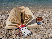 Book, eyeglasses, cup of coffee, cigarettes. Holiday - book, eyeglasses, cup of coffee, cigarette on stone beach Royalty Free Stock Image