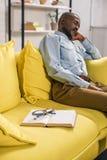 Book and eyeglasses on sofa and senior man. Sleeping behind royalty free stock image