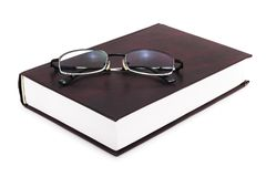 Book with Eyeglasses on White Stock Image