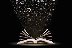Book with falling letters. An open book with letters falling into the pages Stock Photo