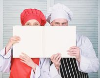 Book family recipes. Cooking guide. According to recipe. Manand woman chef hide faces behind open book. Guy and girl stock photos