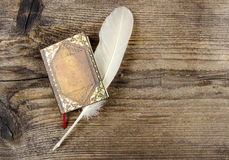 Book and feather on wooden rough background Royalty Free Stock Images