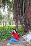 book flickaavläsning Den blonda härliga unga kvinnan med boken sitter under träd utomhus- solig dag royaltyfria foton