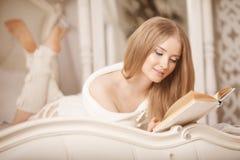 book flickaavläsning Härlig ung kvinna som ligger på soffareadien Arkivbild