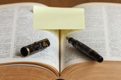 Book with a fountain pen ink with post-it notes. Read a book and point -out  the words with a fountain pen ink Stock Photos