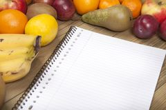 Book and fruits on wooden surface Royalty Free Stock Photos