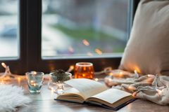 Book, garland lights and candles on window sill. Hygge and cozy home concept - book, garland lights and candles on window sill Stock Photo