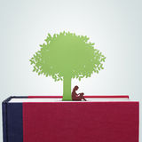 Book with girl reading under the tree paper cut. Reading under a tree is fun Stock Photo