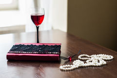 Book, glass of wine, beads. Book decorated with maroon and white beads and a glass of red wine is on a brown table Stock Photography