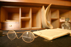 Book and glasses. Old book and glasses on a desk Royalty Free Stock Image