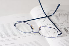 Book and glasses. Glasses on a finance book Royalty Free Stock Photos