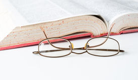 Book and glasses. Glasses and open English dictionary Royalty Free Stock Images