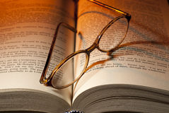 Book and glasses. Reading glasses on open book with orange light in background Stock Images