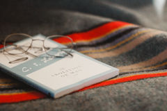 Book and glasses on blanket Royalty Free Stock Image