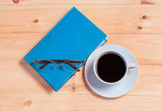 Book, glasses and coffee cup on  wooden background. Top view Royalty Free Stock Photo