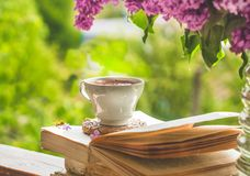 Book, glasses, cup of tea and lilac on a wooden window. The bee flies beautifully over the lilac petals. Fragrant tea in the garden. Romantic concept. Vintage royalty free stock photos