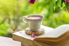 Book, glasses, cup of tea and lilac on a wooden window. The bee flies beautifully over the lilac petals. Fragrant tea in the garden. Romantic concept. Vintage royalty free stock images
