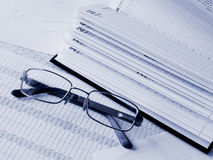 Daily book and glasses on financial figures. Toned blue. Shallow DOF Royalty Free Stock Image