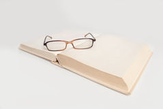 Book with glasses isolated on white Royalty Free Stock Photography