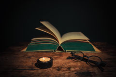 Book and glasses lit by candle. An open book and some glasses at night by candle light Stock Images