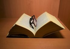 Book and glasses at night Royalty Free Stock Photo
