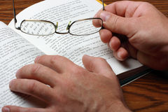 The book and glasses. The open book and the hands holding glasses Stock Photography