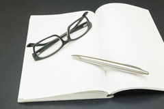 Book with glasses and a pen Stock Photo