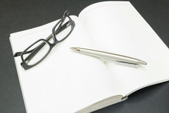 Book with glasses and a pen Stock Photos