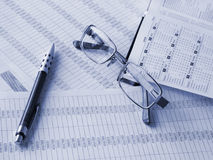 Daily book, glasses, pen on financial figures. Toned blue. Shallow DOF Stock Photos