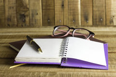 Book with glasses and pen on the wooden background Stock Photography