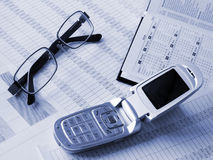 Daily book, glasses, phone on financial figures. Stock Photos