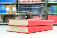 Book and glasses on table in library Stock Image