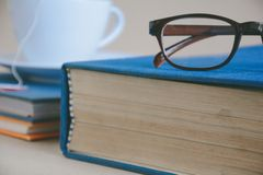 Book glasses and tea on the desk with study and education concep Stock Image