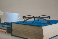 Book glasses and tea on the desk with study and education concep Royalty Free Stock Images