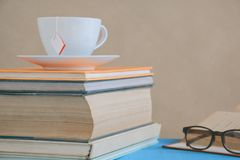 Book glasses and tea on the desk with study and education concep Royalty Free Stock Photo