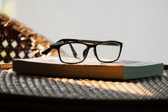 Book and glasses on top of rattan furniture, in modern house  Royalty Free Stock Image