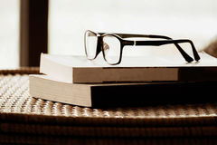 Book and glasses on top of rattan furniture, in modern house wit Royalty Free Stock Photography